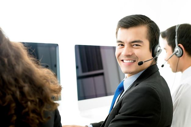 Agente masculino sonriente del servicio de atención al cliente del telemarketing en centro de atención telefónica