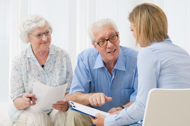 Agente de negocios planeando con una pareja jubilada sus inversiones futuras