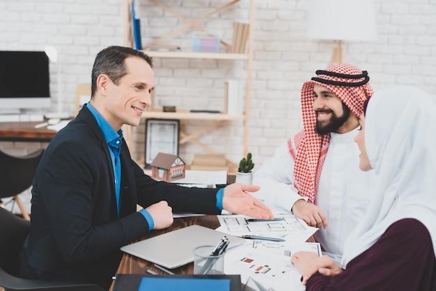El agente propone el plan del apartamento a los clientes musulmanes.