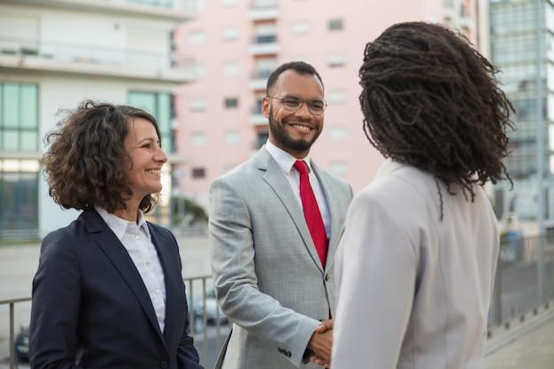 Agente reuniéndose con clientes cerca del edificio de oficinas