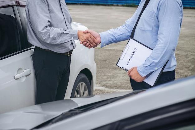 Agente de seguros y el cliente estrecharme la mano, el accidente de tráfico y el concepto de seguro