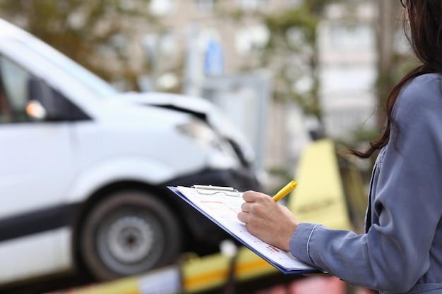El agente de seguros llena la documentación después del accidente.