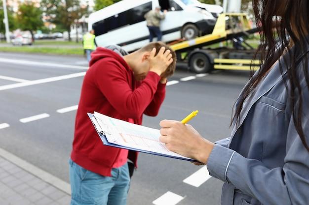 El agente de seguros llena el seguro después de que el conductor del accidente automovilístico esté parado junto a él y sosteniendo su cabeza