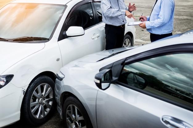 Agente de seguros que escribe en el tablero mientras que examina el coche después de accidente