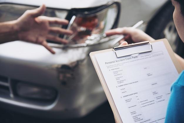 Agente de seguros que trabaja durante el proceso de reclamo de accidentes automovilísticos en el lugar, reclamo de seguro de personas y automóviles
