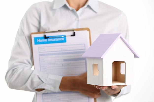 Agente de seguros tiene contrato de seguro y concepto de protección de propiedad residencial de alojamiento