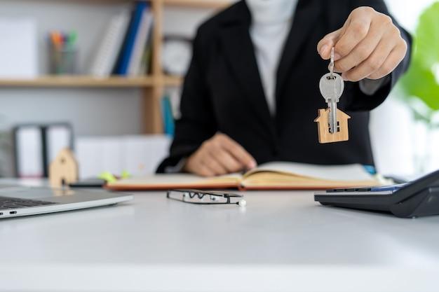 Agente de seguros de vivienda o vendedor con una llave de la casa entregada a un nuevo propietario. venta de casas concepto de bienes raíces y propiedad.