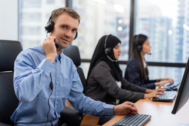Agente de servicio al cliente joven con auriculares trabajando en la computadora en un centro de llamadas