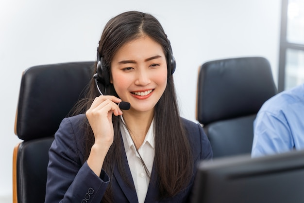 Agente de servicio al cliente mujer asiática con auriculares trabajando en equipo