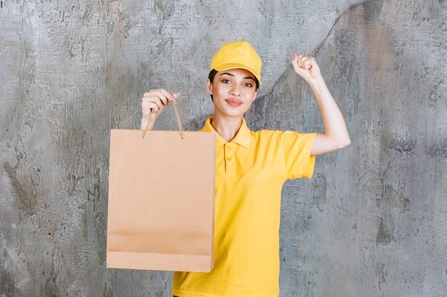 Agente de servicio femenino en uniforme amarillo sosteniendo una bolsa de compras y mostrando un signo de mano positivo.
