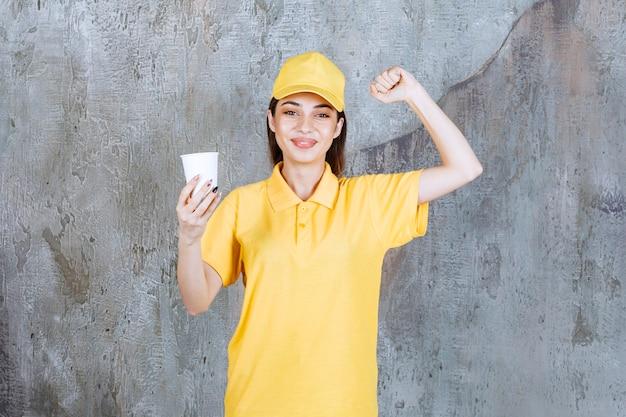 Agente de servicio femenino en uniforme amarillo sosteniendo un vaso de plástico y mostrando un signo de mano positivo.