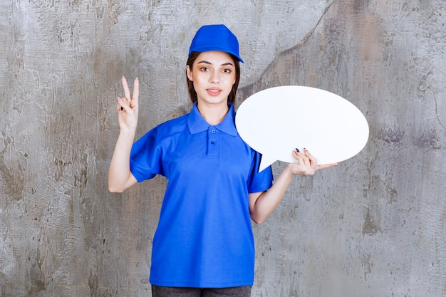 Agente de servicio femenino en uniforme azul sosteniendo un tablero de información ovale y mostrando un signo de mano positivo.