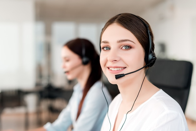 Agente de soporte técnico sonriente con auriculares contestando llamadas de negocios en la oficina de la empresa