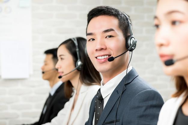 Agente de telemarketing asiático masculino sonriente del servicio de atención al cliente en centro de atención telefónica