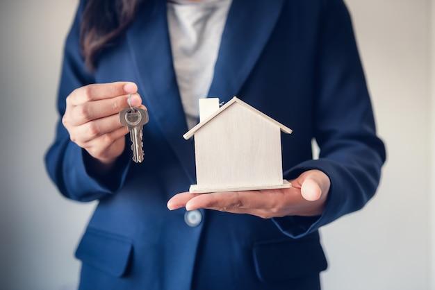Agente de venta de bienes inmuebles entregando llaves de vivienda a clientes.