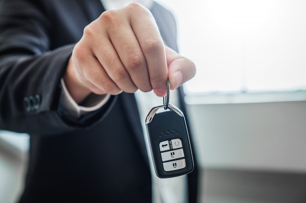 Agente de ventas que da la llave del auto al cliente y firma el contrato de contrato, el seguro del auto.