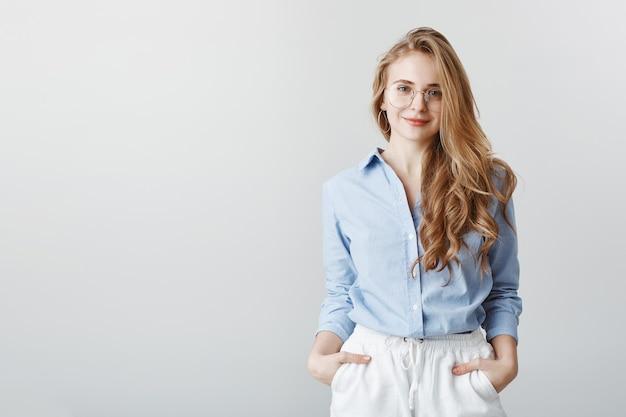 Agente de viajes que escucha los deseos del cliente. retrato de atractiva empresaria europea en blusa azul y gafas, tomados de la mano en los bolsillos y sonriendo, siendo amable y educado sobre la pared gris