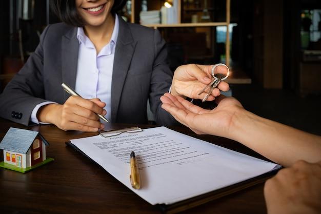 Los agentes están entregando las llaves de la casa del cliente después de firmar el contrato en la oficina de la agencia.