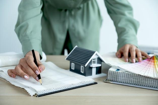 Agentes inmobiliarios e interiores presentan casas y cortinas para decoración de interiores.