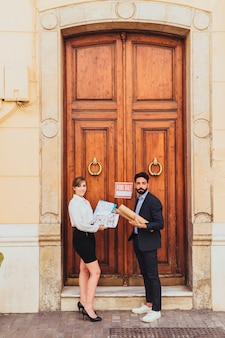 Agentes inmobiliarios posando en la puerta principal