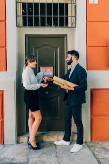 Agentes inmobiliarios sonrientes intercambiando llaves