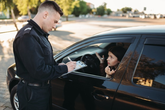 Agentes de policía masculinos comprueban el vehículo en la carretera