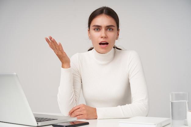Agitada joven hermosa dama morena en poloneck blanco mirando confusamente a la cámara y levantando perpleja su palma, sentada a la mesa con una computadora portátil moderna