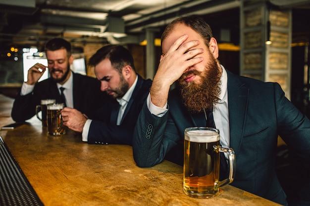 Agotado y triste joven barbudo cubren la cara con la mano. se sienta en la barra del bar. jarra de cerveza está ahí. otros dos hombres se sientan detrás.
