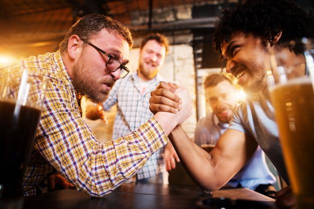 Agotados amigos varones de raza mixta que tienen un desafío de lucha libre en el bar local mientras otros apoyan.