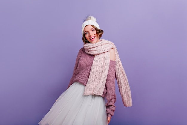 Agraciada chica blanca en bufanda larga y cálida de pie en la pared púrpura. refinada mujer joven complacida con sombrero posando con sonrisa.