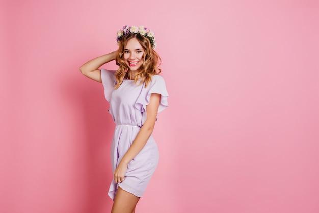 Agraciada mujer blanca en corona posando en pared rosa