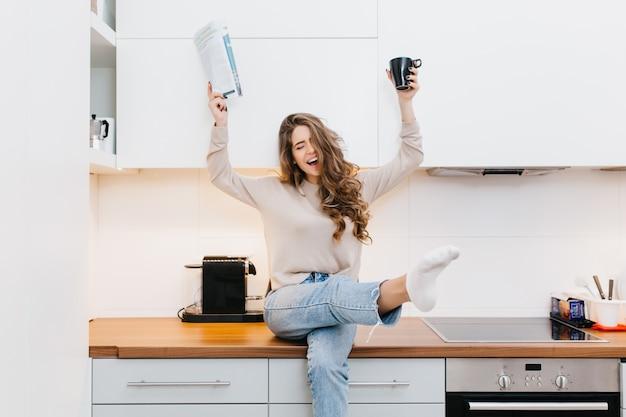 Agraciada niña caucásica usa jeans disfrutando de buenos días en su cocina