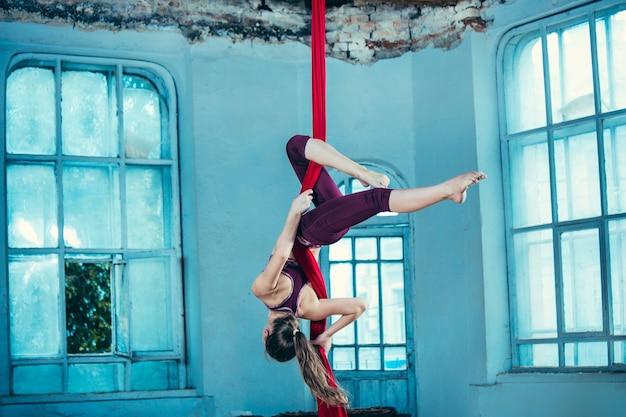 Agraciado gimnasta realizando ejercicio aéreo con telas rojas