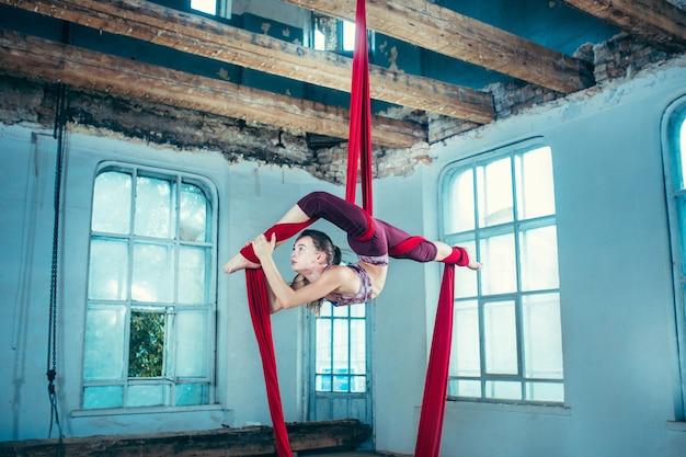 Agraciado gimnasta realizar ejercicio aéreo con telas rojas sobre fondo azul loft antiguo.