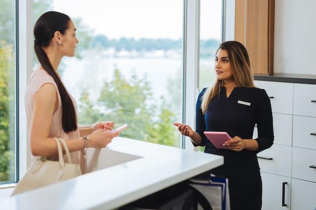 Agradable agradable mujer sosteniendo una tableta mientras habla con el cliente en el salón de belleza