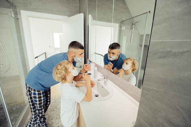 Agradable buen hombre enseñando a su hijo a afeitarse