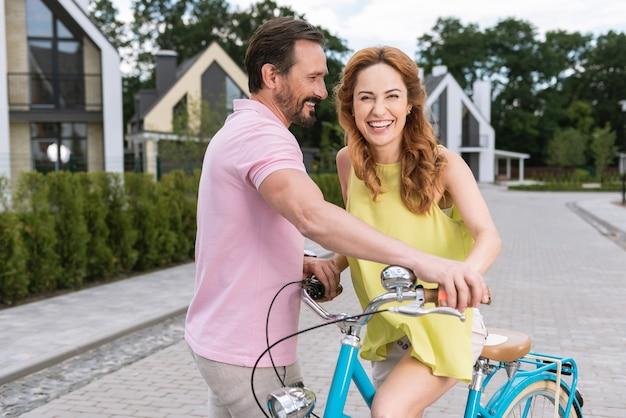 Agradable buen hombre sosteniendo una bicicleta mientras ayuda a su novia