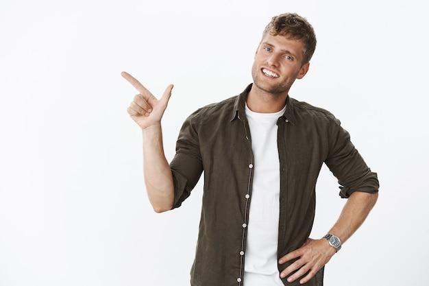 Agradable y carismático novio rubio apuntando a la izquierda como mostrando alrededor de nuevo apartamento sonriendo amigable al frente sosteniendo la mano en la cintura durante una conversación informal y relajante sobre una pared gris