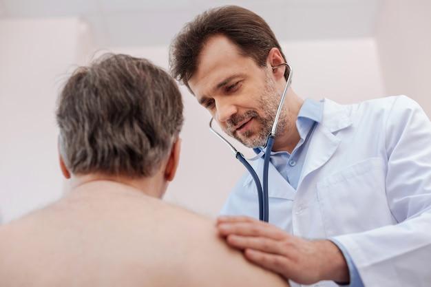 Agradable y destacado médico inteligente que averigua el diagnóstico de los pacientes mediante el uso de un estetoscopio y estimula la respiración del paciente.