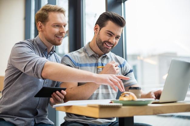 Agradable hombre agradable alegre sosteniendo una tableta y apuntando a la pantalla del portátil mientras muestra una imagen a su amigo
