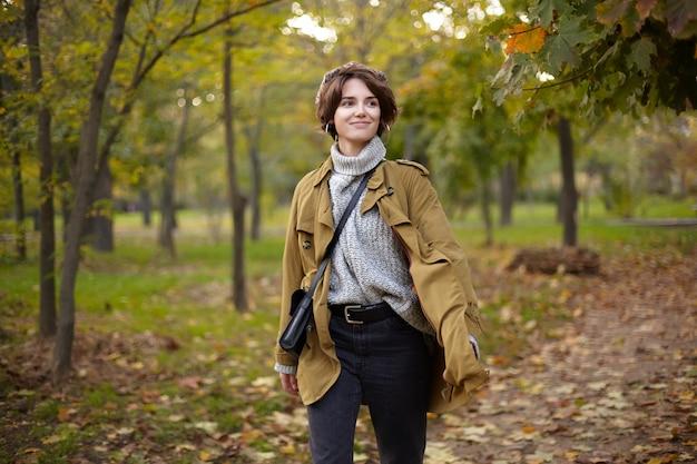 Agradable joven alegre hermosa mujer morena de pelo corto sonriendo positivamente mientras camina por el jardín de la ciudad, se encuentra con amigos el fin de semana y tiene buen humor