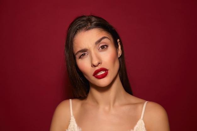 Agradable joven bastante alegre dama morena de pelo largo con labios rojos