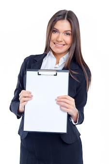 Agradable joven empresaria sosteniendo la hoja de papel en blanco para copiar el espacio aislado en la pared blanca