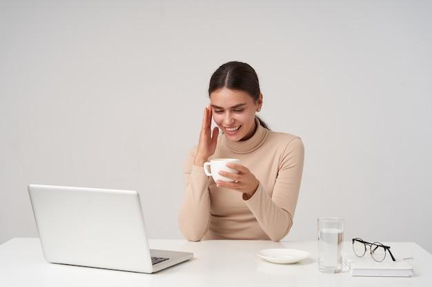Agradable joven encantadora dama de cabello oscuro tomando café mientras toma un descanso, tiene un buen día y sonríe alegremente, sentado en la oficina moderna sobre una pared blanca