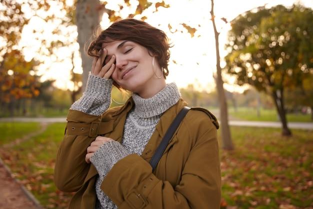 Agradable joven encantadora mujer morena de pelo corto manteniendo la mano levantada en la cara y sonriendo suavemente con los ojos cerrados mientras posa sobre el jardín de la ciudad en un cálido día de otoño