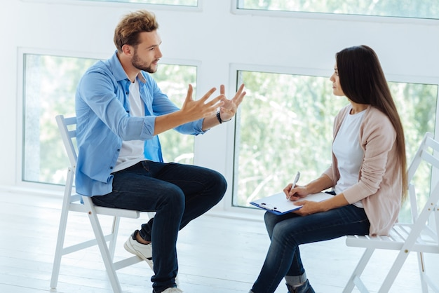 Agradable joven gesticulando y explicando su problema mientras habla con un terapeuta