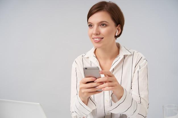 Agradable joven morena de pelo corto y ojos marrones sonriendo positivamente con el teléfono inteligente en las manos levantadas, vestida con ropa formal elegante mientras posa en blanco