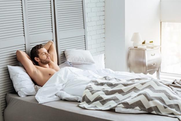 Agradable mañana. apuesto joven bien construido descansando la cabeza sobre las manos y acostado en su cama mientras disfruta de la mañana