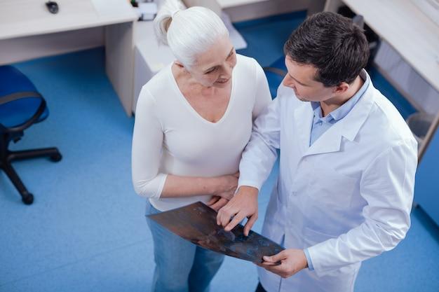 Agradable médico guapo positivo de pie cerca de su paciente y hablando con ella mientras le muestra la foto de rayos x