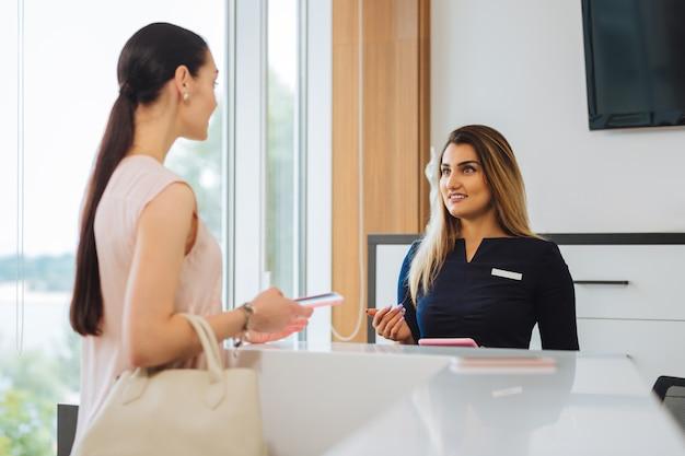 Agradable mujer agradable hablando con la recepcionista mientras tiene una cita en el salón de belleza